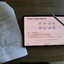 Schreibtisch von Professor Göddeke von oben. Darauf liegt ein Tablet, auf dem ein Skript zu sehen ist, und Arbeitsmaterial in Papierform.
